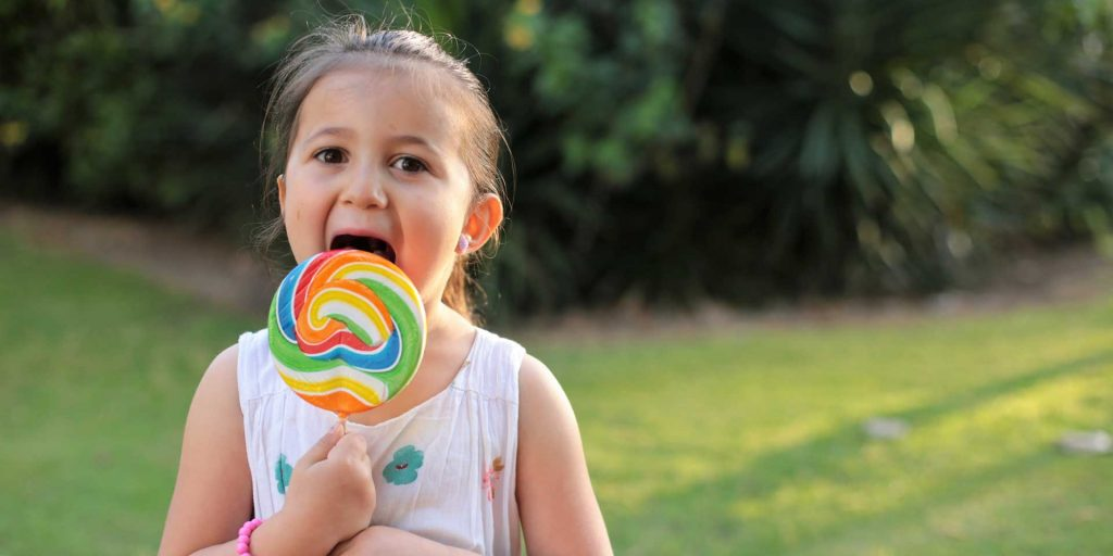 Girl licking a giant lollypop - all that sugar could lead to cavities.